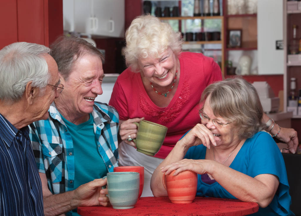 A groups of older friends giggle over coffee
