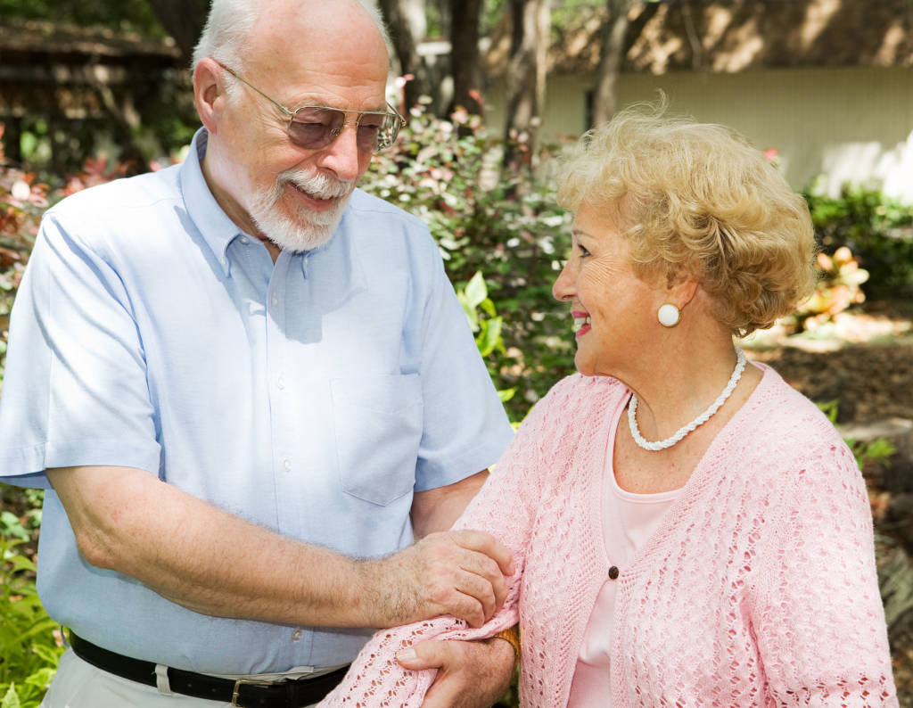 Older man holding arm of older woman