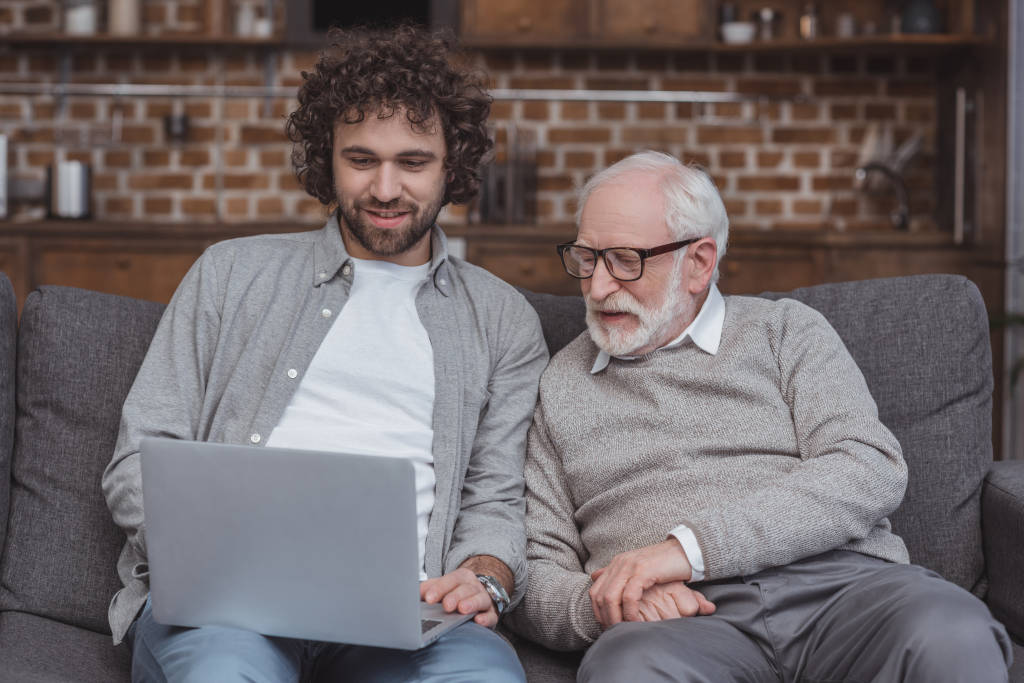 Younger man shows older man/father his laptop