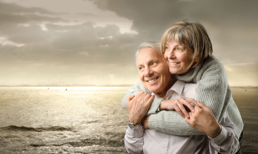 Older couple hugging besides estuary