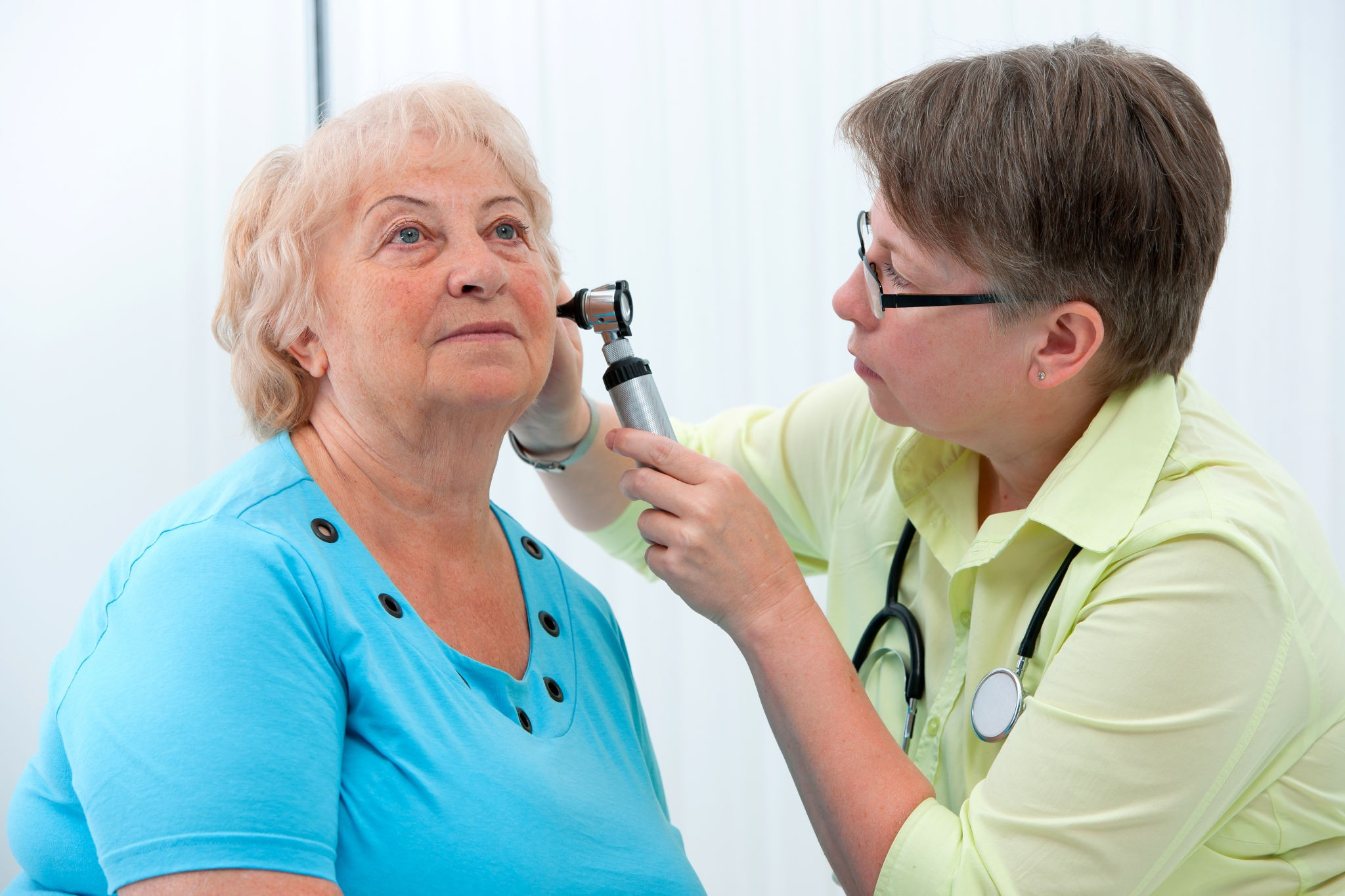 Woman having ear examined by doctor